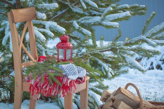 Scandinavian style wool mittens on Christmas plaid and chair near basketful of firewood