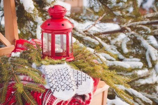 Scandinavian style wool mittens on Christmas plaid near firewood and red lantern