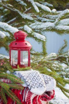Scandinavian style wool mittens on the Christmas plaid near red lantern