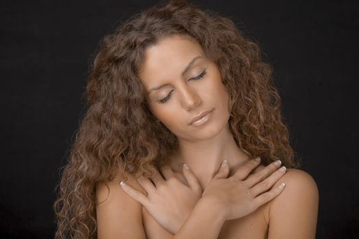 A beauty shot of a gorgeous young female with curly brown hair. Eyes closed.