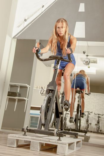 Young beautiful woman in a cycling gym on a bike, looking to camera.