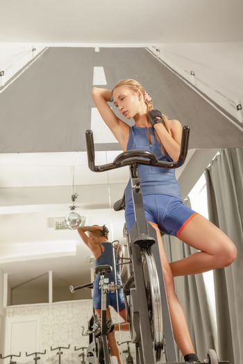 Young beautiful female stretching while resting in a cycling gym.