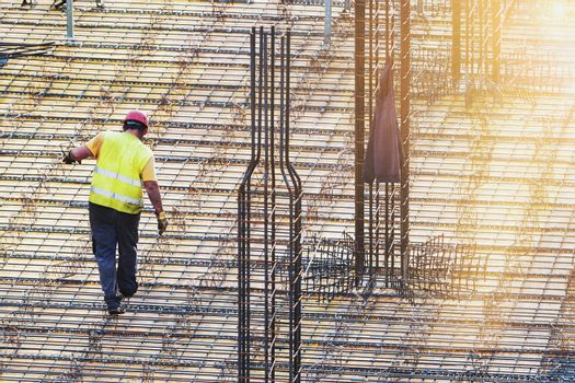 One man worker doing metal work at construction site with early morning sun rays