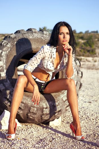 the beautiful girl poses on a tire in desert at hot day