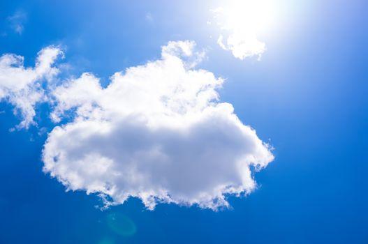 The sun is bright shining blue through a small cloud. Cumulus clouds in the blue sky. The sun shines through white cloud.