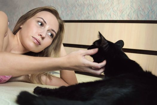 girl with a cat. Beautiful blonde girl lying in bed and Gulati his black cat in the bright morning light. Care for the animal. love for Pets