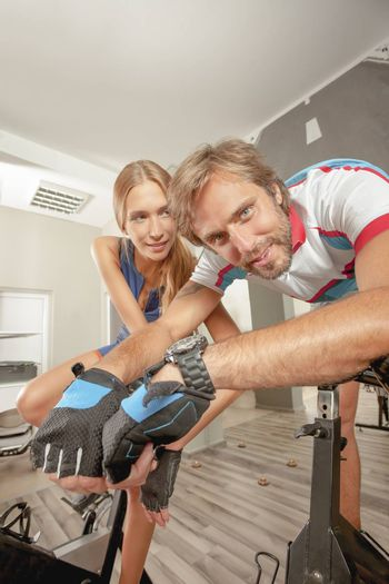 Young beautiful female and handsome male having fun in a cycling gym.