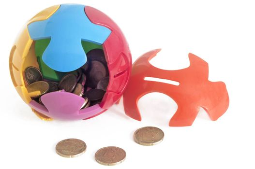 puzzle-shaped piggy bank and some coins