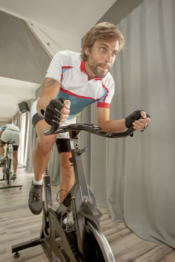 Young handsome determined man training in a cycling gym.