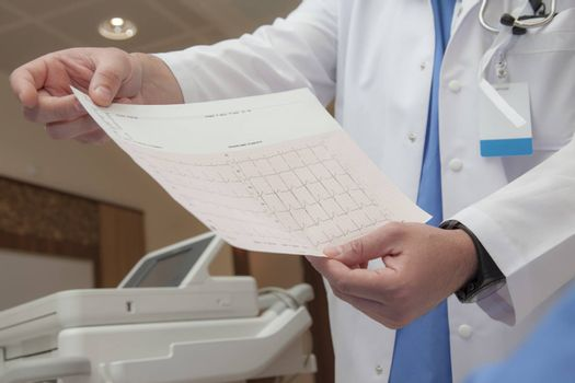 A doctors hand are holding a graph with an unconfirmed diagnosis of normal heart rate.