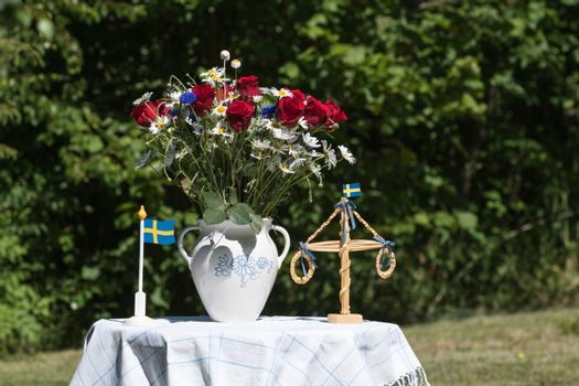 Table decorated with flowers and miniatures for midsummer celebration outdoors in a garden