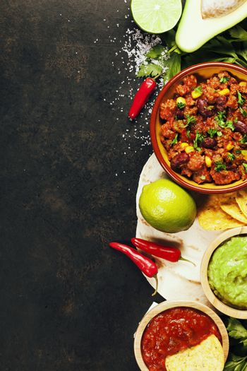 Mexican food concept: tortilla chips, guacamole, salsa, chili with beans and fresh ingredients over vintage rusty metal background. Top view