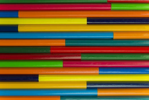 Collection of coloured pencils in a horizontal complementary colors set up as background picture