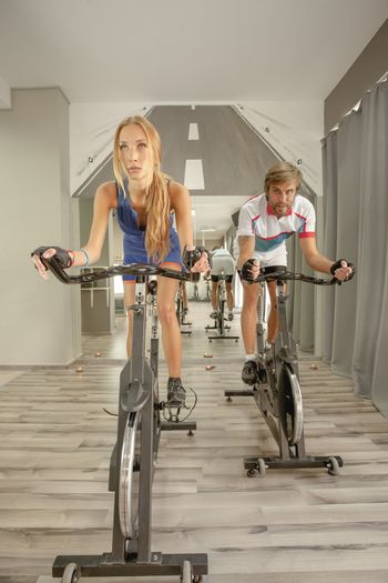 Young beautiful female and a male cycling in a fitnes.