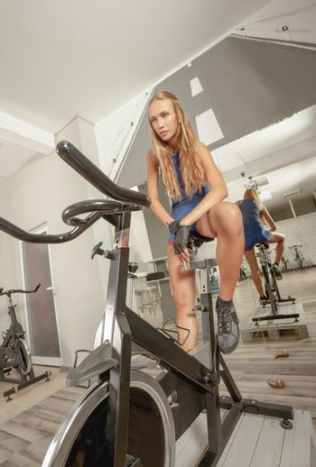 Young beautiful sexy female resting on a bike in a cycling gym.