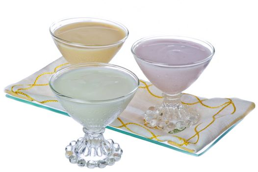 three cups of yogurt in different flavors