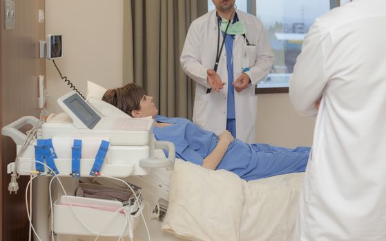 A patient is listening to a doctor, hand and torso only, in modern hospital.