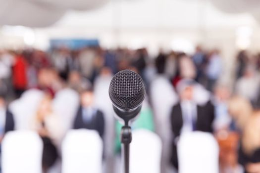 Participants at the business or professional conference. Microphone in focus against blurred audience.