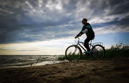 Image of sporty one tourist man walking along the shore with the bike against sunset sky with clouds and sun rays.
