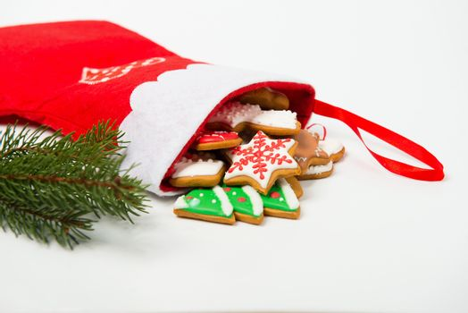 Christmas concept. Christmas sock with gingerbread and christmas tree branch on white background