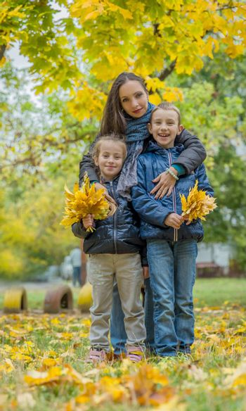 Mother hugging two children among autumn forest
