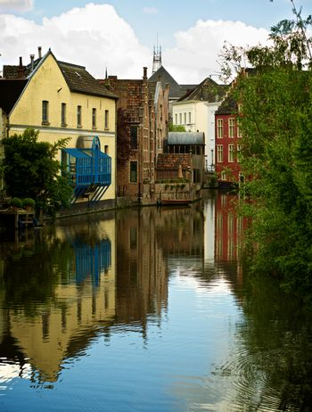 River Cityscape with Colorful Houses and Reflection on Water Outdoors. Ghent, Belgium