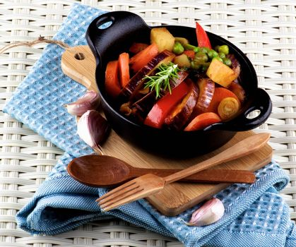 Delicious Homemade Colorful Vegetables Ragout with Eggplant, Carrots, Potatoes, Leek, Bell Pepper and Green Pea in Black Iron Cast with Wooden Spoon and Fork closeup on Blue Napkin