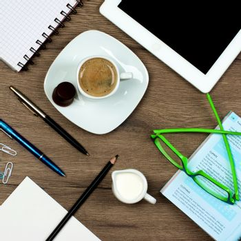 Coffee Break Concept with Coffee Cup, Stationery Items, Digital Tablet and Greens Eyeglasses closeup on Wooden background. Top View