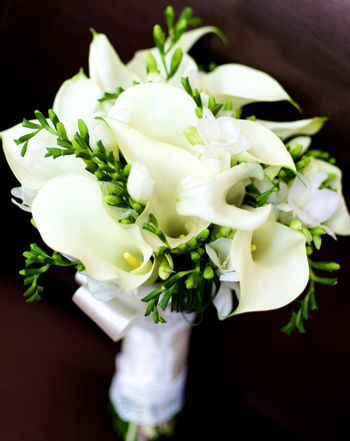 Beautiful Bridal Bouquet with Callas, Snowdrops and Green Buds and Satin Ribbon closeup on Dark background. Focus on Pestle of Calla