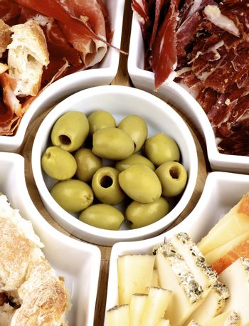 Serving Plate with Spanish Snacks, Jamon, Various Cheeses, Bread Sticks, Cured Ham and Green Olives Cross Section