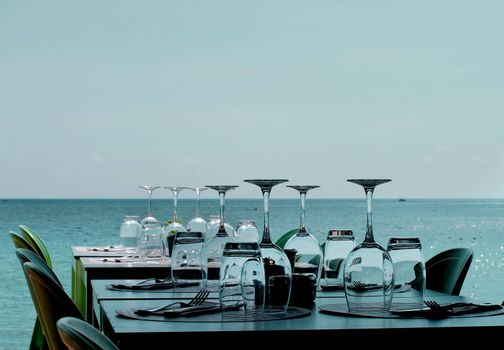 Elegant Restaurant Tables with Various Stemware and Silverware on Terrace in Shadow on Sea Coast Outdoors. Turquoise Toned