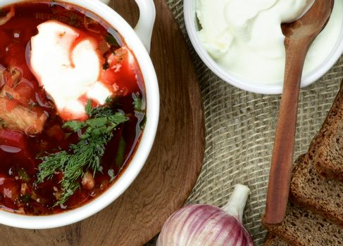 Ukrainian National Traditional Beet Soup Borscht with Brown Bread, Garlic and Sour Cream on Wooden Plate with Wooden Spoon. Top View