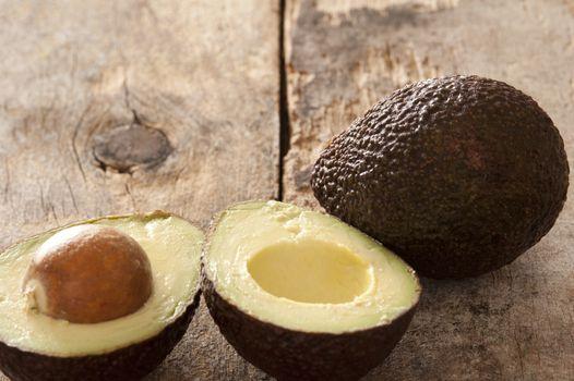 Tasty whole and halved ripe avocado pears