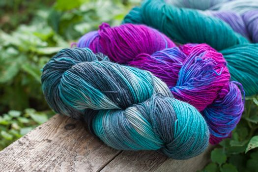 Colourful wool yarn balls on the wooden background