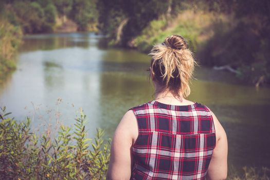 Back view of woman standing and looking away at banks of the river. Relaxation and meditation concept.
