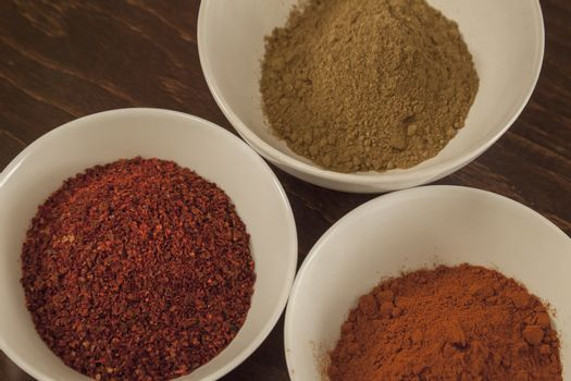 Three cups with different ethiopian spicy - red chilli and sweet pepper, berbere in background