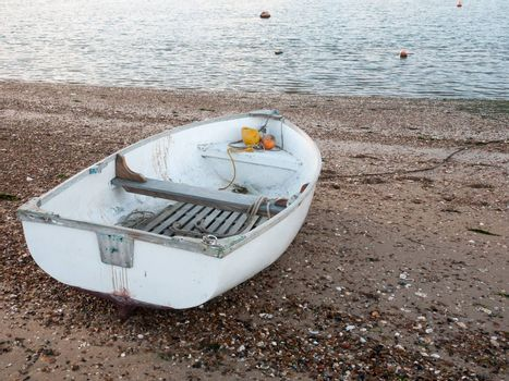 small white private boat parked moored on beach front bay ; west mersea, essex, england, uk