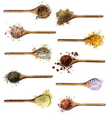 Collection of Various Spices in Wooden Spoons: Coriander,  Dried Paprika, Salt with Chili and Petals, Thyme, Cumin and Curry Powders, Dried Chili and Kosher Salt isolated on White background