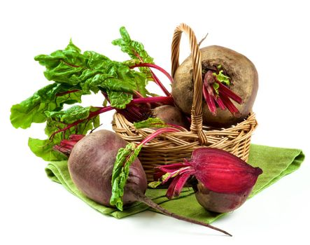 Arrangement of Full Body Fresh Raw Organic Beet Roots and and One Half with Green Beet Tops in Wicker Basket on Napkin isolated on White background