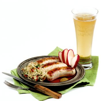 Delicious Grilled White Munich Sausages with Pickled Cabbage, Chopped Radish and Glass of Beer on Green Napkin isolated on White background