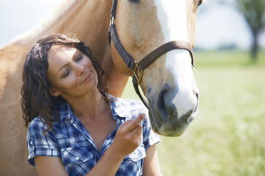 Woman and horse together at paddock