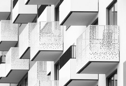 Modern architectural abstract with balconies and windows, black and white residential building facade picture
