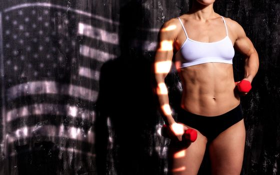 Strong woman with red barbells, dark background with the USA fla
