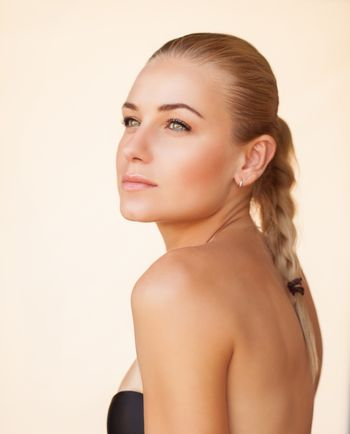 Fashion portrait of a beautiful blond girl with bare makeup over beige background, natural beauty of a woman face with a healthy skin,  sensual look