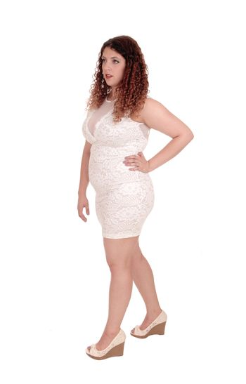 A young gorgeous woman in a beige lace dress walking isolated for white background with her hand on her hip.