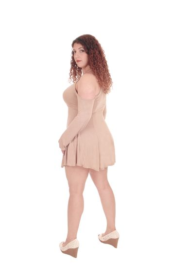 A beautiful Caucasian woman standing in a beige dress from the back, looking over her shoulder, isolated for white background.