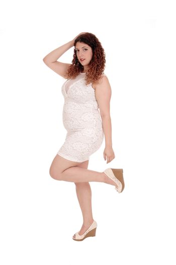 A beautiful young woman with curly brunette hair standing with one leg up, isolated for white background.