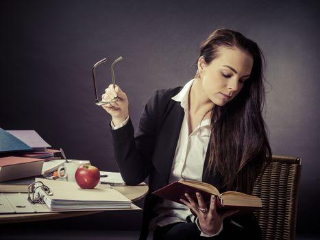 Teacher sitting at her messy desk reading