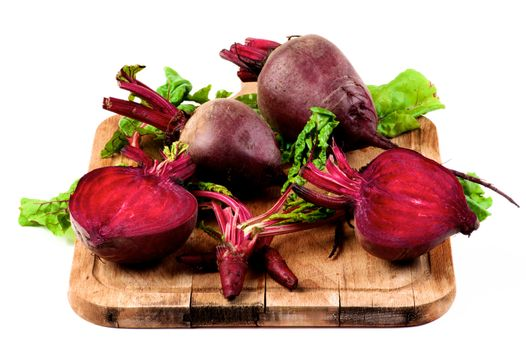 Arrangement of Fresh Raw Organic Beet Roots Full Body, Halves and Young Sprouts with Green Beet Tops closeup on Wooden Cutting Board isolated on White background