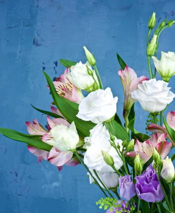 Elegant Flowers Bouquet with White and Purple Lisianthus, Alstroemeria and Decorative Green Stems closeup on Blue Textured background